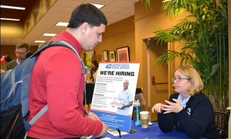 Student at an on-campus career fair, talking to a recruiter.