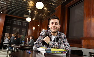 Male student working with a young child in a classroom setting.