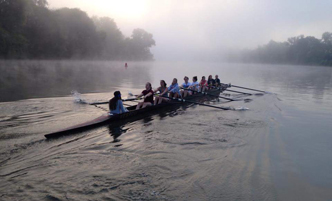 Women's crew in an 8-person boat on a misty river.