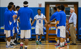 Men's basketball team members giving high-fives before the start of a game.