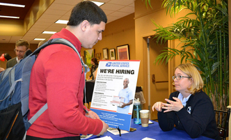 Student speaking with a recruiter at an employment fair.