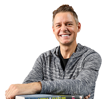 Man sitting with books in front of him, smiling at the camera.