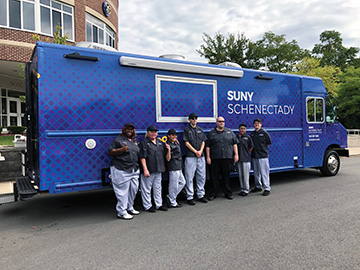 Student and faculty standing in front of the SUNY Schenectady food truck.