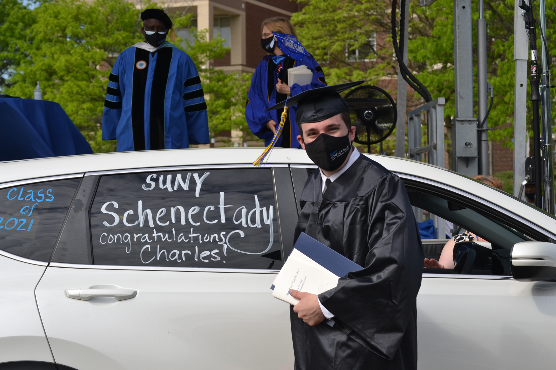 Charles, a graduate, in cap and gown near car.