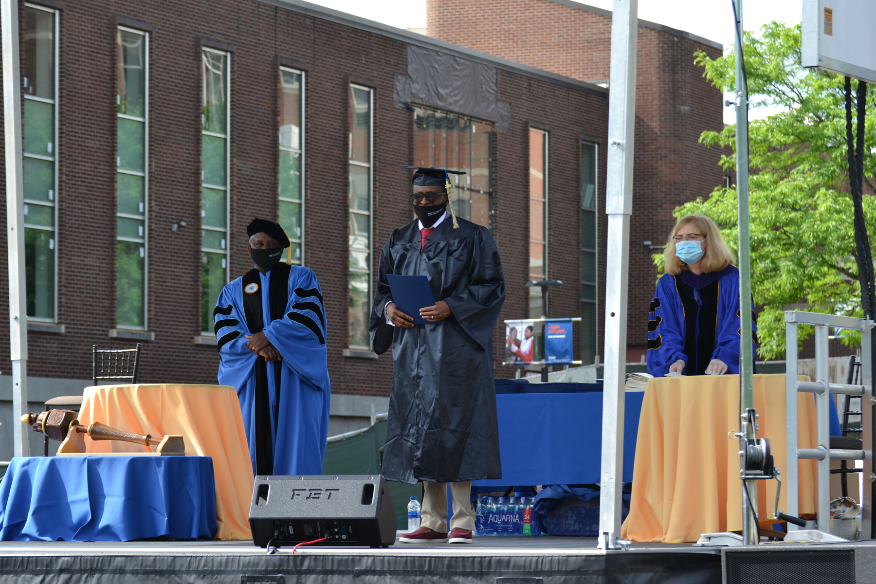 Graduate Olujide Adesina holding up diploma on stage