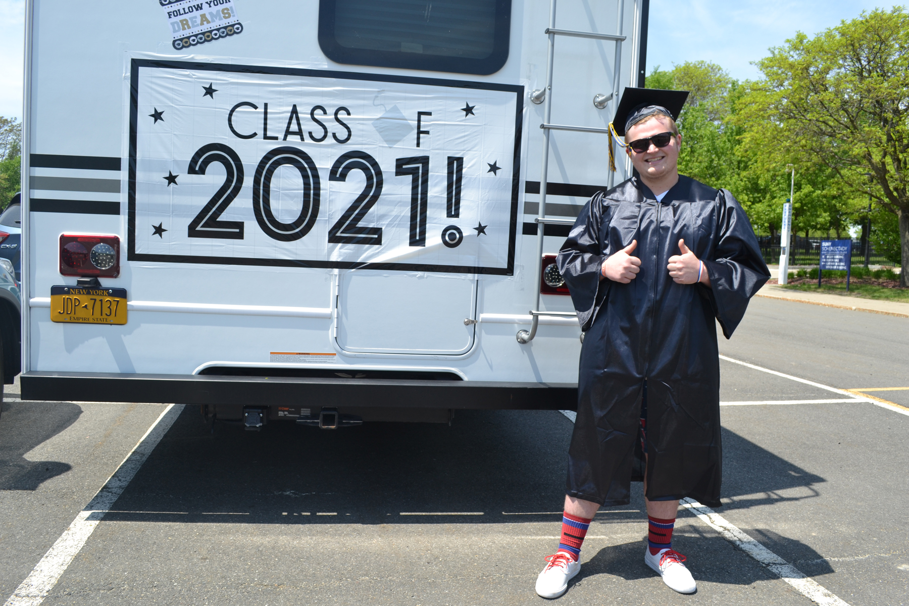 William Gross in cap and gown near RV.